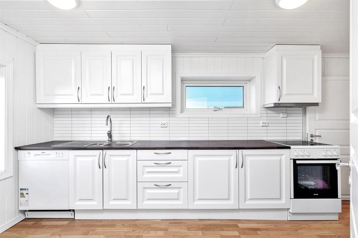 Pent kjøkken med lyse fronter med god skap- og benkplass