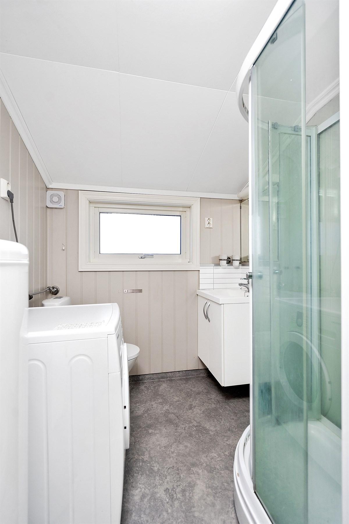 Bad i lyse farger med dusjkabinett og lys baderomsinnredning
