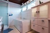 Bad med badekar, dusjkabinett, toalett og innredning med servant