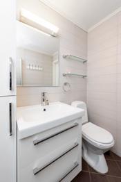 Baderommet er innredet med frittstående toalett, dusjhjørne med foldbare glassvegger og vask med underskap.