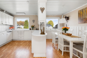 Kjøkkensonen defineres av en stilfull kjøkkeninnredning med hvitevarer som er bruksvennlig plassert.
