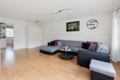 Stuen har god plass for sofamøblement, TV-seksjon og spisestue .