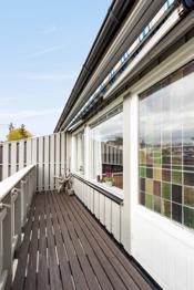 Balkongen med utsikt over hage. Markise for solskjerming