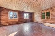 Boligen har en romslig stue med originale tømmervegger.