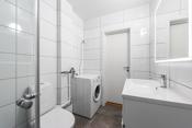 Baderommet er innredet med frittstående toalett, dusjhjørne med innfellbare glassvegger, vask med underskap og opplegg for vaskemaskin.