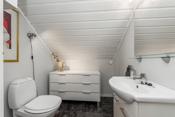 Toalettrom i 2. etasje er lyst innredet med en hvit servantinnredning med speil over.