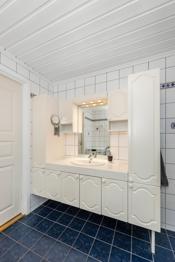 Hvit baderomsinnredning med speil, overskap og to høyskap.