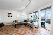 Rommet har utgang til den solrike terrassen som forlenger stuen på solfylte sommerdager.