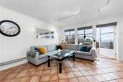 Åpen stue- og kjøkkenløsning som har flislagt gulv og hvor det er varmekabler. Det er også montert varmepumpe.