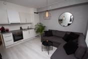 Åpen løsning mellom stue og kjøkken. Kjøkkenet har integrerte hvitevarer.