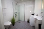 Pent flislagt bad av god størrelse. Badet er utstyrt med dusjhjørne, toalett, servant med servantskap, speil med lys, opplegg til vaskemaskin med overskap og høyskap.