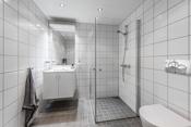 Bad 2 er et lyst og pent flislagt bad.