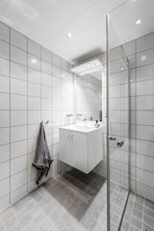Badet er dusjhjørne, servant med servantskap og toalett. Downlights i tak og varmekabler i gulv.