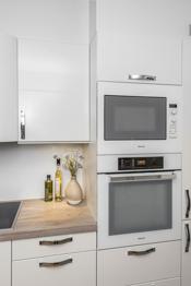 Lyst og pent kjøkken med integrerte hvitevarer.