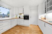 Kjøkkenet ligger i et separat rom ved stuen. Fin kjøkkeninnredning fra Sentrum kjøkken med hvite profilerte fronter.