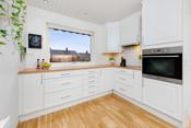 Fliser på vegg mellom overskap og kjøkkenbenk. Lys under overskap.