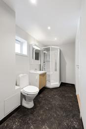 Baderom er innredet med toalett, dusjkabinett og vask med over- og underskap.