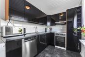 Kjøkkensonen defineres av stilfull kjøkkeninnredning med svarte slette fronter og laminerte benkeplater.