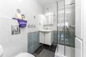 Baderommet er innredet med vegghengt toalett, dusjkabinett, servant med underskap, og over servanten er det speil med belysning.
