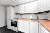 Kjøkken i underetasjen er innredet med profilerte hvite fronter og laminerte benkeplater med nedfelt oppvaskkum.