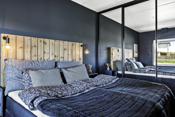 Soverom med en veldig god størrelse og en stor skyvedørgarderobe med speildører.