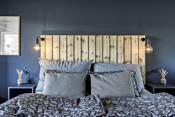 Det er fastmontert en stilig sengegavl og veggmonterte nattbord som medfølger.