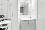 Lys baderomsinnredning med tilhørende speil over og høyskap.