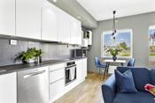 Hvit kjøkkeninnredning med integrert komfyr og koketopp