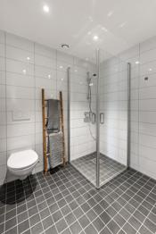 Bade er utstyrt med toalett, servant med skuffer, dusjhjørne og opplegg til vaskemaskin.