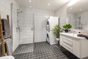 Lyst bad med fliser på vegger og gulv med gulvvarme.