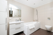 Flislagt bad i underetasjen er moderne innredet med downlights i taket, hvit baderomsinnredning med tilhørende speil over og høyskap.