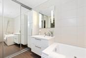 Det er badekar og vegghengt toalett. Praktisk skyvedørsgarderobe med speildører hvor det er opplegg for vaskemaskin og tørketrommel.