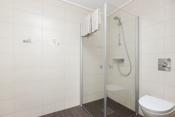Flislagt og delikat bad i 1. etasje med dusjhjørne, downlights i taket og vegghengt toalett.