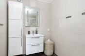 Flislagt bad i 1. etasje har hvit baderomsinnredning med tilhørende spiel over og høyskap.