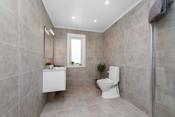 Fra entré er det direkte inngang til flislagt bad i som nylig er oppgradert og er lekkert innredet med stor fliser på gulv og vegger.