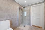 Det er montert dusjhjørne, hvit baderomsinnredning med tilhørende speil over og vegghengt toalett.