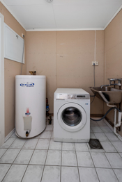 Praktisk, separat vaskerom i underetasjen som har flislagt gulv med varmekabler og inngang til bod..