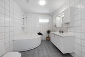 Flislagt bad i underetasjen har hjørnebadekar, toalett og en romslig, hvit baderomsinnredning med tilhørende speil og skap over.