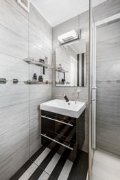 . Baderommet er innredet med dusjkabinett, speilskap og vask med underskap.