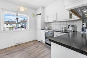 Kjøkkenet defineres av en stilfull kjøkkeninnredning der de fleste hvitevarene er bruksvennlig plassert.