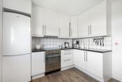 Kjøkkeninnredning med hvite profilerte fronter, laminerte benkeplater og fliser mellom under- og overskap.