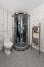 Badet er utstyrt med servant, speil, skap, dusjkabinett, toalett og opplegg til vaskemaskin.