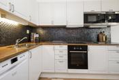 Kjøkkenet har integrerte hvitevarer som stekeovn, platetopp, mikro og kaffemaskin.