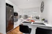Kjøkkensonen defineres av moderne kjøkkeninnredning med lyse slette fronter, i kontrast til mørke fliser mellom overskap og benkeplater.