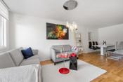 Stuen er et lyst og luftig rom takket være hvitmalte vegger og store vindusflater som fyller rommet rikelig med daglys.