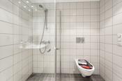 Badet er utstyrt med servant, toalett og dusjhjørne.