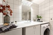 Badet har servant med servantsakp og skuffer, opplegg til vaskemaskin, toalett og dusjhjørne.