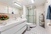 Flislagt bad i underetasjen har en moderne baderomsinnredning med skuffer og tilhørende speilskap over.
