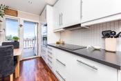 Lyst kjøkken med hvite fliser over laminat benkeplater og godt med skapplass.