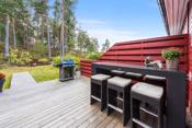 På baksiden av boligen er det en hyggelig terrasse og hage som vender mot rolige skogsområder.
